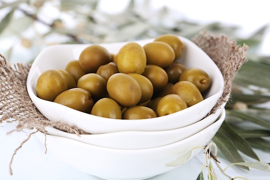 Olives in bowl with branch close up